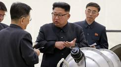 Kim Jong Un, centre, is continuing banned nuclear activities, the UN experts say (Korean Central News Agency/Korea News Service/AP)