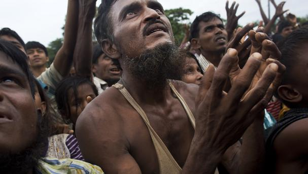 So hungry: A Rohingya refugee stretches his arms out for food at Kutupalong, Bangladesh (AP)