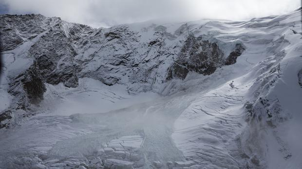 Glacial ice avalanche of the Trift Glacier above the village pictured as part of it broke off and tumbled below (Dominic Steinmann/Keystone via AP)