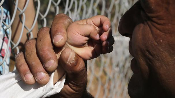 Ammar Hammasho, a migrant from Syria who lives in Cyprus, holds the hand of one of his four children after they arrived with their mother at a refugee camp in Cyprus (AP/Petros Karadjias)