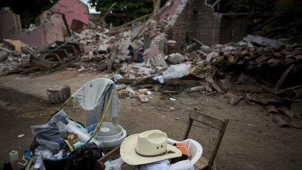 A handful of salvaged items in front of what remains of a home destroyed in Asuncion Ixtaltepec, Oaxaca state (AP)