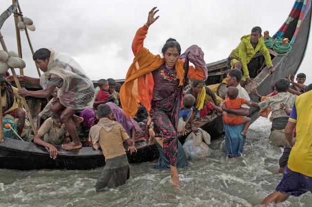 Rohingya refugees jump from a wooden boat as it begins to tip over after travelling from Myanmar. Photo: Getty Images