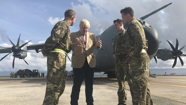 Boris Johnson talks to the pilots of an RAF A400M aircraft in Barbados, where he stopped on his way to visit British territories ravaged by Hurricane Irma
