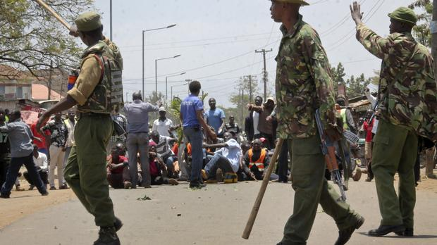 Kenyan police prevent opposition protesters who had blocked roads and thrown rocks from trying to storm a hotel in Kisumu (AP)