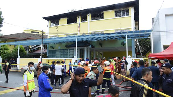 Police and rescue personnel work at the school cordoned off after the fire on the outskirts of Kuala Lumpur (AP)