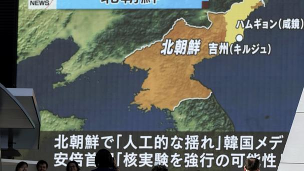 People walk past a TV news report on North Korea's possible nuclear test, in Tokyo (AP)