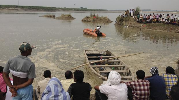 Rescuers search in the Yamuna River and villagers gather after a country boat, seen in the foreground, capsized near Baghpat town in Uttar Pradesh state, India (AP)