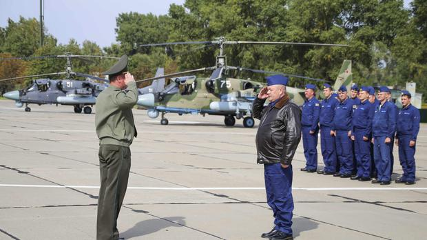 Russian military pilots, right, report upon arrival at an airbase at an undisclosed location in Belarus (Vayar Military Agency photo via AP)