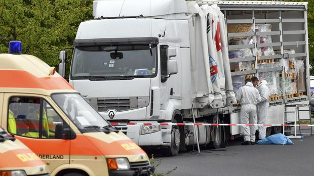 Policemen investigate a truck in eastern Germany which had with 51 people squeezed inside (Patrick Pleul/dpa via AP)