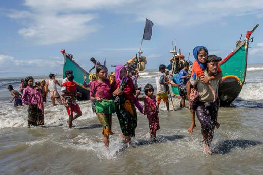 EXODUS: Rohingya Muslims walk to the shore after arriving on a boat from Myanmar to Bangladesh. Photo: Dar Yasin/AP
