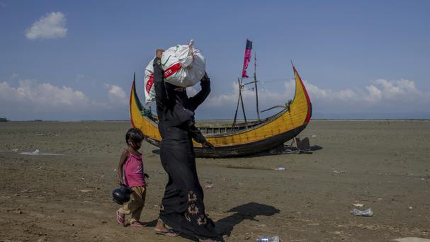 A Rohingya Muslim woman, who crossed over from Myanmar into Bangladesh, walks with her daughter after receiving aid material in Teknaf, Bangladesh (AP)