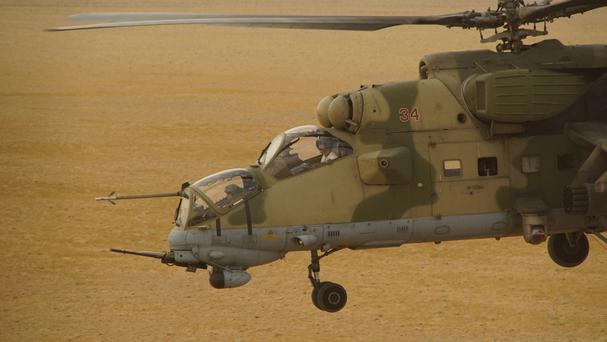 A Russian military helicopter flies over a desert in Deir el-Zour province