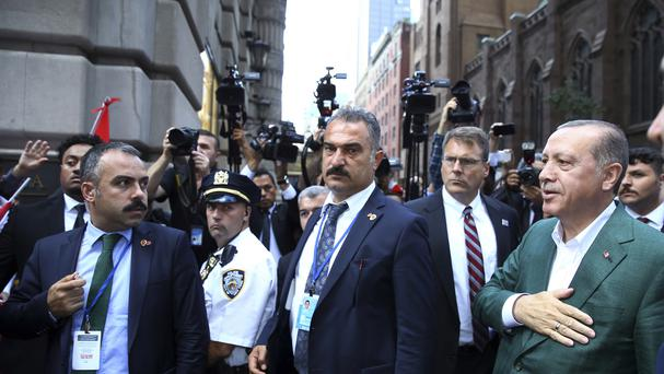 Recep Tayyip Erdogan, right, acknowledges supporters as he arrives at his hotel in New York for the UN General Assembly (AP)