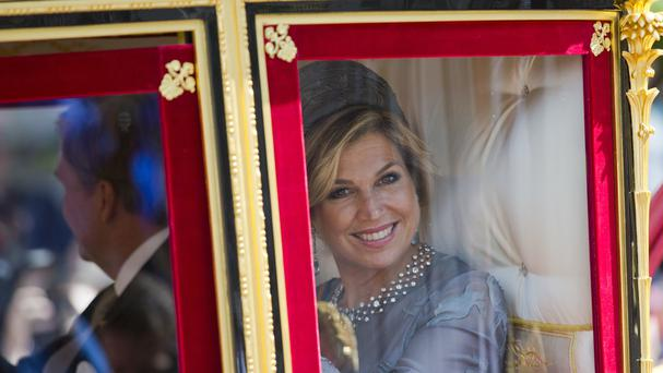 Dutch Queen Maxima, right, and King Willem-Alexander, left, wave to well-wishers from a horse-drawn carriage as they arrive back at the royal palace Noordeinde in The Hague, Netherlands (AP)