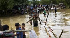 Rohingya Muslims, who crossed over recently from Burma into Bangladesh, cross a flooded area to find alternate shelter after their camp was inundated with rainwater (AP)