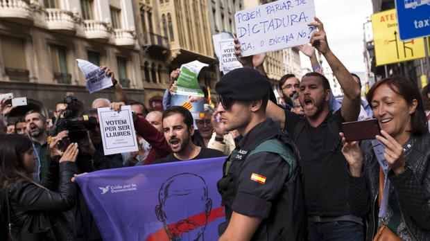 A Civil Guard officer stands guard in front of one of the offices of the Catalonian government as demonstrators shout pro-independence slogans in Barcelona (AP)