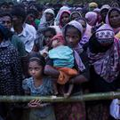 Rohingya Muslims, who crossed over recently from Burma into Bangladesh, stand in queues to receive food being distributed near Balukhali refugee camp in Cox's Bazar (AP)
