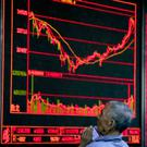 A Chinese man holds his smartphone as he monitors stock prices at a brokerage house in Beijing (AP)