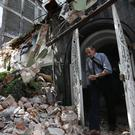 A man walks through a door frame of a building that collapsed during the 7.1-magnitude earthquake, in the Condesa neighborhood of Mexico City (AP Photo/Marco Ugarte)