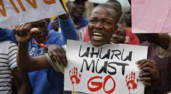 A supporter of opposition leader Raila Odinga holds a poster referring to President Uhuru Kenyatta (AP)