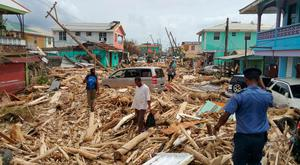 Locals survey the damage caused by Hurricane Maria in Roseau, Dominica. Photo: Getty Images
