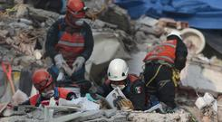 Rescue workers search for survivors in the rubble of a building felled by the earthquake (AP Photo/Eduardo Verdugo)