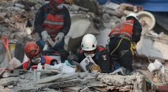 Rescuers search the rubble of a building in the Ciudad Jardin neighbourhood of Mexico City (AP)