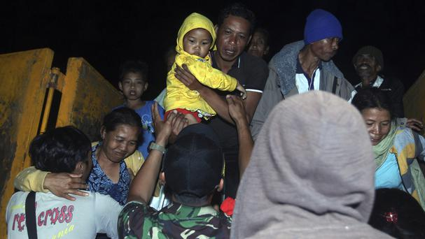 Rescuers help villagers evacuated from their homes on the slope of Mount Agung amid fears the volcano may erupt (AP/Firdia Lisnawati)