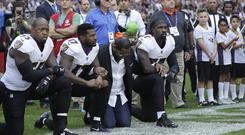 Baltimore Ravens stars kneel during the national anthem