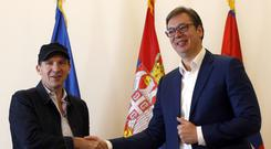 Ralph Fiennes, left, shakes hands with Serbian President Aleksandar Vucic after receiving his passport