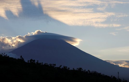 The sun sets behind Mount Agung yesterday. Photo: Reuters