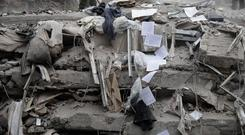 Documents tumble down past collapsed floors of a building in the Del Valle neighbourhood of Mexico City (AP)