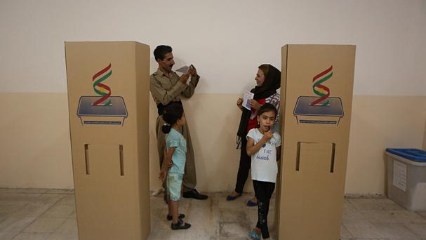 An Iraqi Kurdish man takes a picture for his wife as she shows her voting paper during the referendum on independence from Iraq (AP)