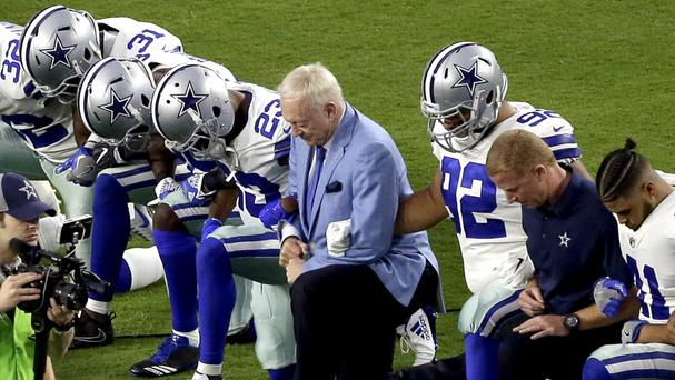 Jerry Jones, centre, takes a knee prior to the national anthem with his Dallas Cowboys team (AP)