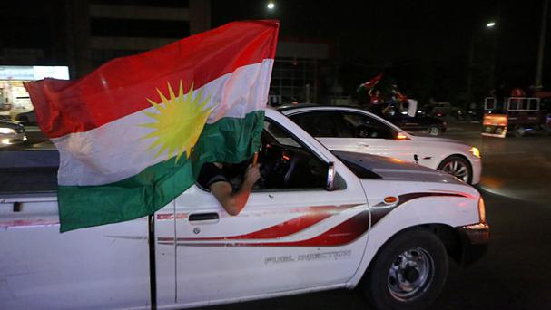 Iraqi Kurdish men celebrate as they wave Kurdish flags in the streets of Irbil (AP)
