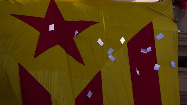 Ballot papers thrown by demonstrators float next to a huge independence flag in Catalonia (AP)