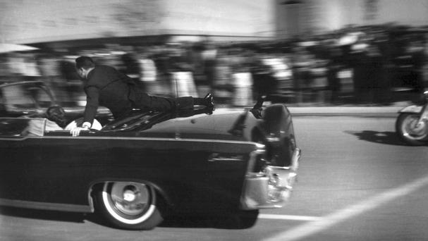 The limousine carrying mortally wounded President John F. Kennedy races toward the hospital seconds after he was shot in Dallas with Secret Service agent Clinton Hill riding on the back of the car (AP)