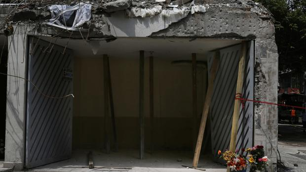 Flowers are placed next to the garage, the only structure that remains of a building collapsed in last week's 7.1 earthquake at the Condesa neighbourhood of Mexico City (AP).