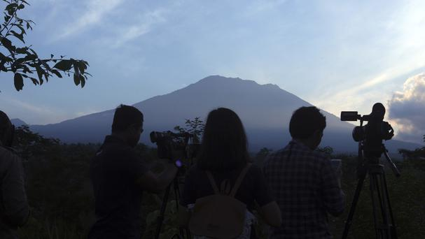 Journalists watch the Mount Agung volcano from an observation point (AP Photo/Firdia Lisnawati)