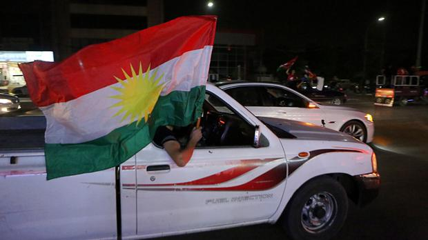 Iraqi Kurdish men celebrate as they wave Kurdish flags in the streets after the polls closed in the controversial referendum (AP)