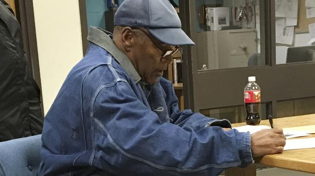 OJ Simpson signs documents before his release (Nevada Department of Corrections/AP)