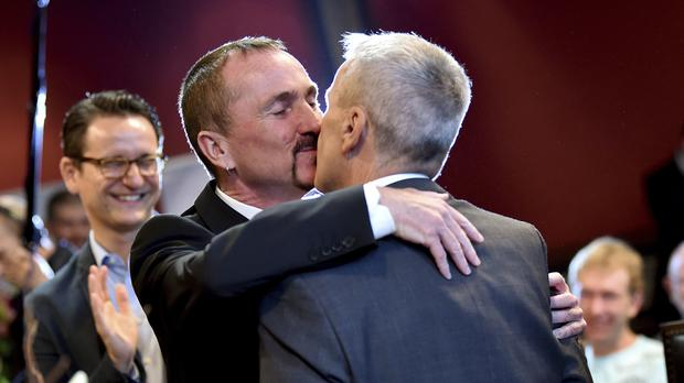 Karl Kreile, left, and Bodo Mende kiss after their marriage in Berlin (AP)