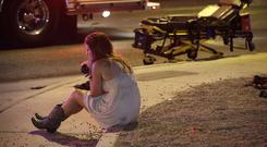 A woman sits on a kerb at the scene of the shooting (AP)