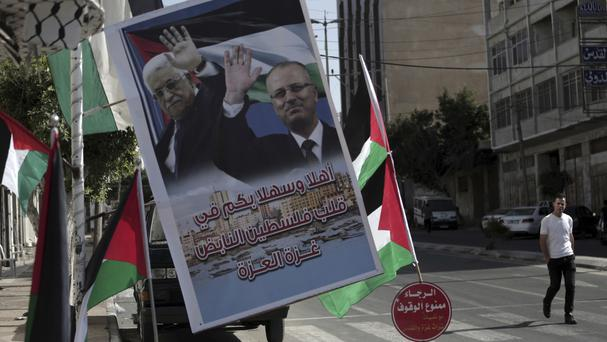 A poster of Palestinian president Mahmoud Abbas and Palestinian prime minister Rami Hamdallah hangs on a street in Gaza City (AP)