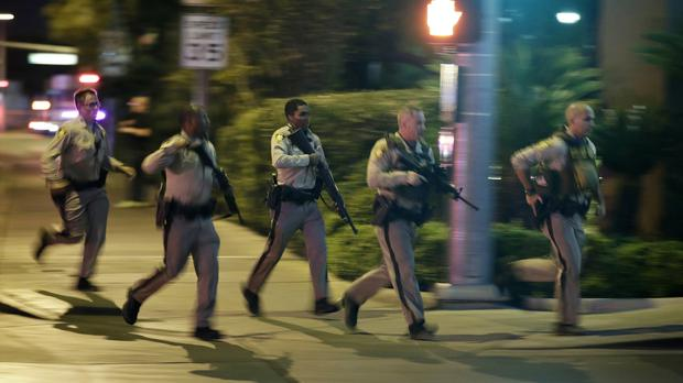 Police run to cover at the scene of a shooting near the Mandalay Bay resort and casino on the Las Vegas Strip (AP Photo/John Locher)