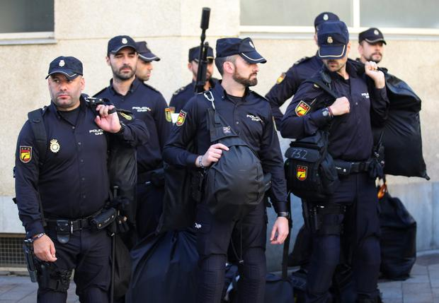 Spanish National Police officers stand in front of their hotel before leaving in police vehicles in Pineda de Mar, Barcelona. Photo: REUTERS