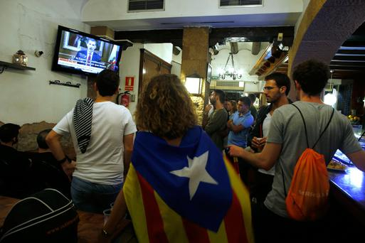 People watch King Felipe's televised statement on TV in downtown Barcelona. Photo: AP
