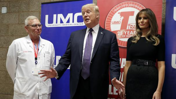 President Donald Trump talks as first lady Melania Trump and surgeon Dr John Fildes listen at the University Medical Center