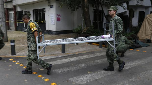 Soldiers cary a cot as they break camp from the earthquake-torn Condesa neighbourhood of Mexico City (AP)