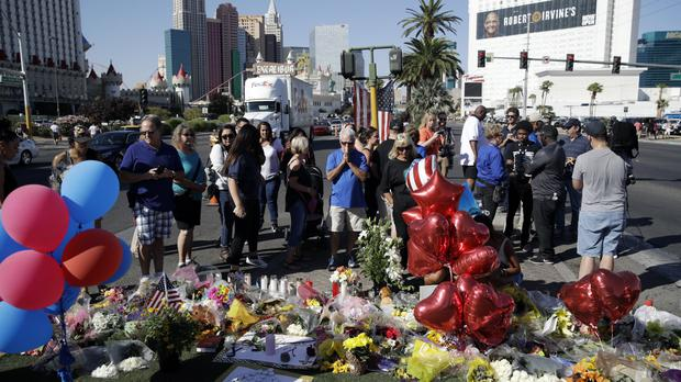 People pause at a memorial for the victims of a mass shooting in Las Vegas (AP)